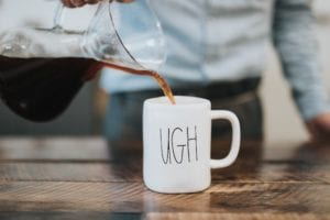 Pouring coffee into an ugh mug.