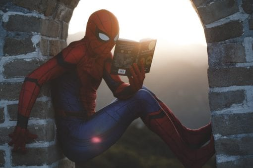 Spiderman reading a book.