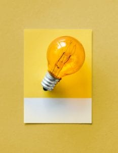 Lit light bulb on yellow background.