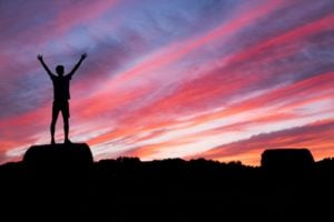 Man standing triumphantly on top of a mountain.